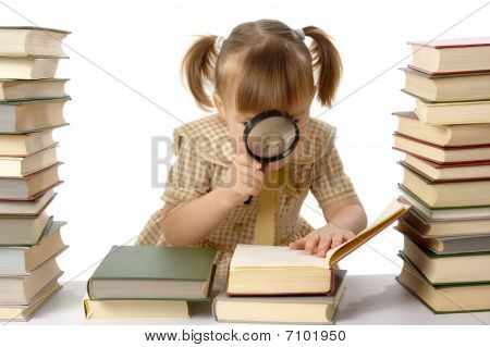 Little girl is looking at books through magnifier