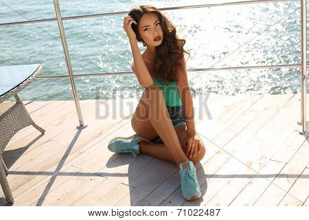 Beautiful Girl With Dark Hair In Sport Clothes Relaxing On Yacht