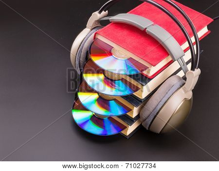 Cd sticks out from red books with headphones on it