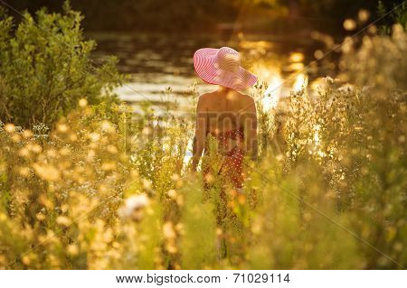 Woman With Hat On The Waterfront On A Summer Evening