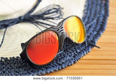 Sunglasses On The Edge Of The Beach Hat On A Wooden Background