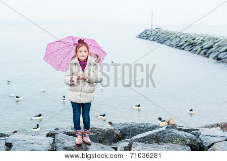 Little girl with umbrella on a rainy day