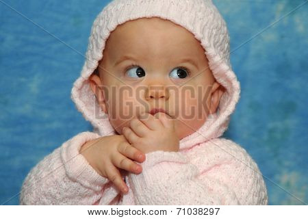 Baby girl sucking fingers as she discovers hands