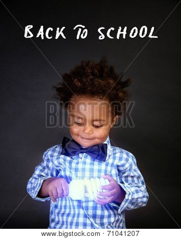 Little smart boy holding in hands bright electrical lamp isolated on black background, innovation in physic, back to school concept