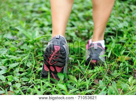 young woman runner legs on geen grass