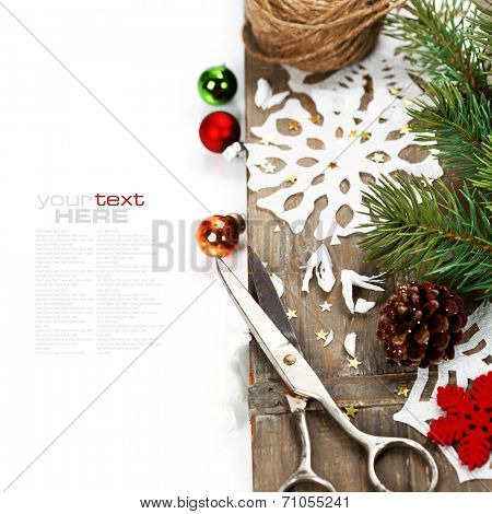 Snowflakes  made of paper and christmas tree on wooden background