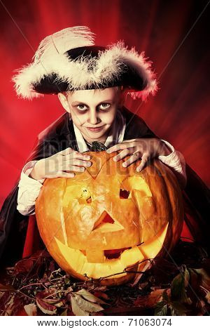 Little boy in halloween costume of pirate posing with pumpkins over dark background .