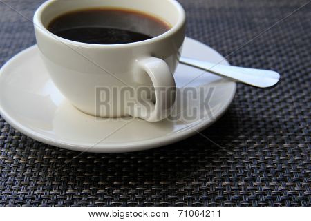 Hot cup of coffee on placemat