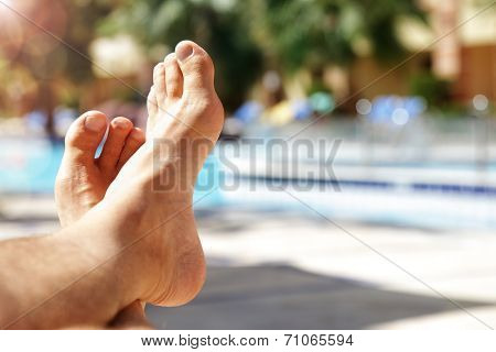 Sunbathing by the hotel tourist resort swimming pool, mans legs lying down on a sunlounger looking over the water