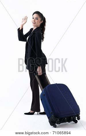 Happy Woman Pulling Her Luggage And Waving Her Hand