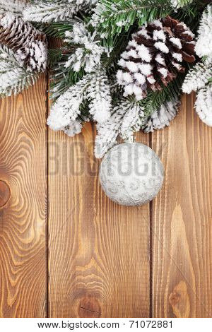 Christmas fir tree with snow and bauble on rustic wooden board with copy space