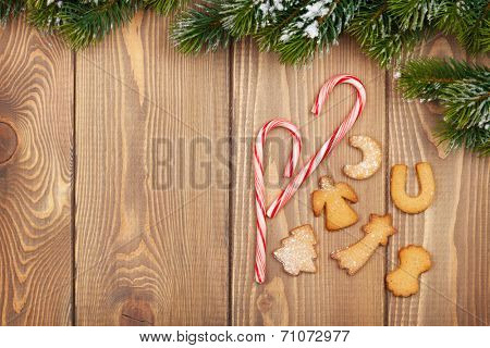 Christmas fir tree with snow, candy cane and gingerbread cookies on rustic wooden board with copy space