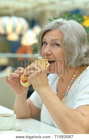 Elderly woman eating fast food