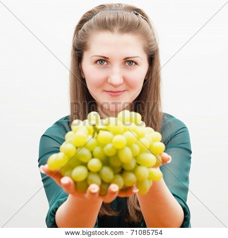 welcoming smiling girl with grapes