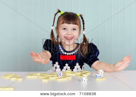 Happy Beautiful Child Plays With Toys On Table