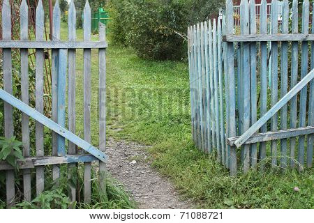 A blue old ragged gate to a dacha garden in a village with ground and grass and trees
