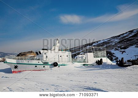 Ship in winter frozen lake