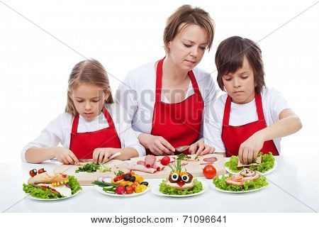 Kids and their mother preparing the party sandwiches - funny food creatures, isolated