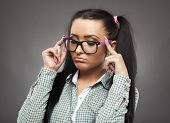 stock photo of sulky  - Sulky girl with nerd glasses and pigtails posing as a spoiled brat on gray background - JPG