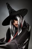 stock photo of sorcerer  - Closeup portrait of a sorcerer with hat and cape over gray background - JPG