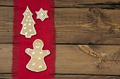 foto of ginger bread  - A Ginger Bread Woman Christmas Tree and Star on Red Drapery on Wooden Background with Copy Space - JPG