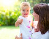 stock photo of mums  - Beautiful Mother And Baby playing in a park - JPG