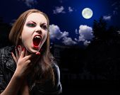 stock photo of terrific  - Vampire woman on night background with moon - JPG