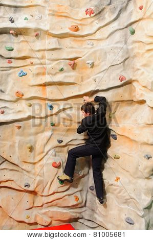 Businessman climbing on man-made cliff in the sport centre