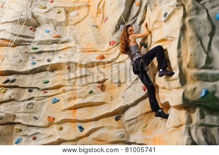 Woman climbing on man-made cliff in the sport centre