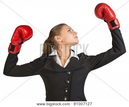Businesswoman wearing boxing gloves, with her arms forward up