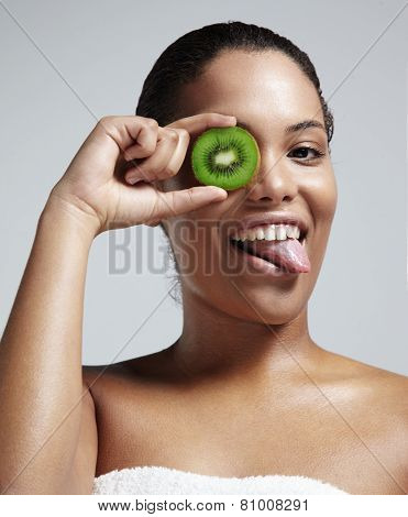 Woman Have Fun With A Facial Treatmens. Holding A Kiwi Slice