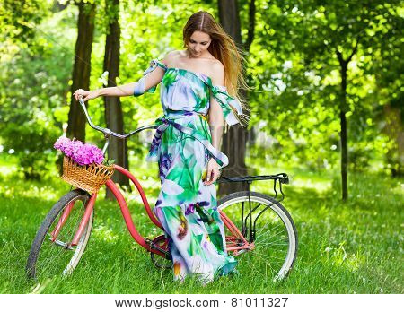 Beautiful Blond Woman Wearing A Nice Dress Having Fun In Park With Bicycle Carrying A Beautiful Bask