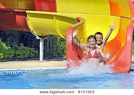 niños deslizándose por un tobogán de agua