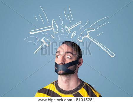 Young man with taped mouth and white drawn beating hammer marks around his head