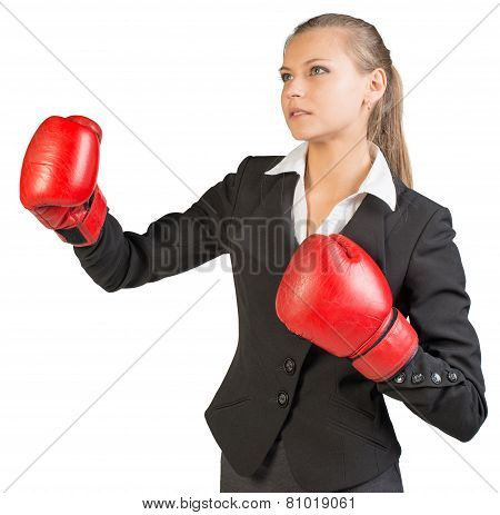 Businesswoman wearing boxing gloves, her lips parted