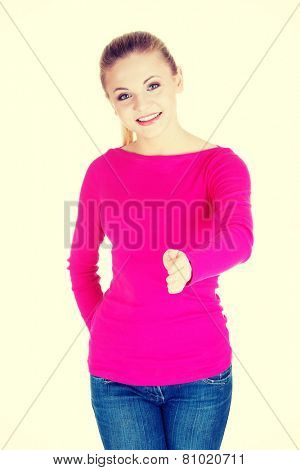 Young casual woman showing welcome gesture. Giving a hand.