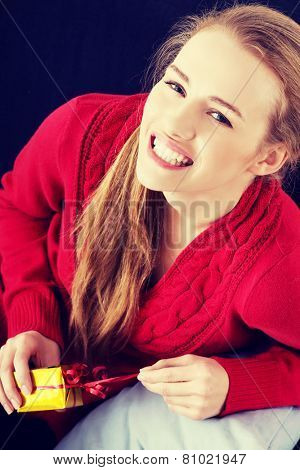 Beautiful woman in red sweater is unwrapping small present.