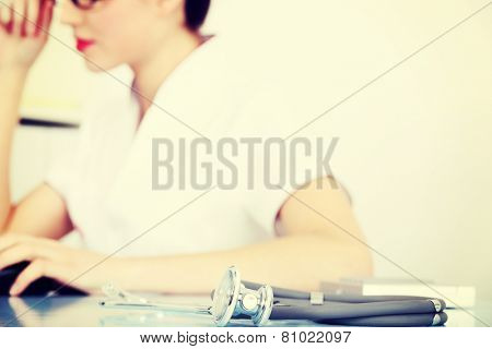Young doctor sitting with stethoscope. Focus on the stethoscope.