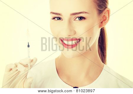 Beautiful young nurse or doctor with needle, shot ready to apply.