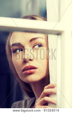 Beautiful woman is looking through window. Indoor background.