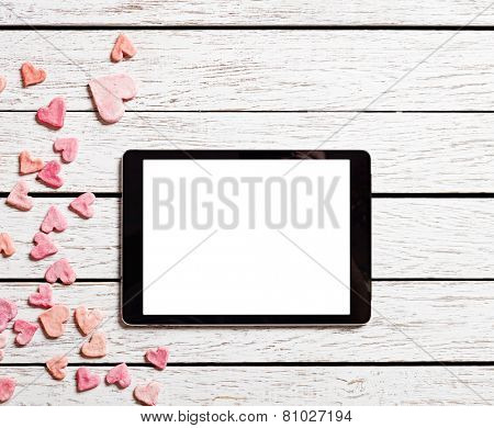 Digital tablet on white wood table with heap of small hearts.