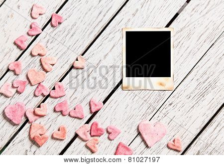 Blank instant photo on white wood table with heap of small hearts.