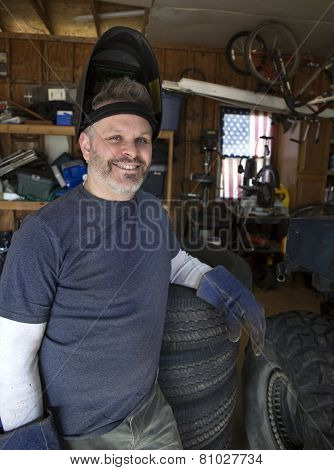 Man wearing welding helmet leaning against tires