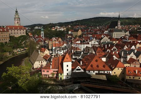 Krummau Castle and St Vitus Church over tiled roofs in Cesky Krumlov, South Bohemia, Czech Republic.