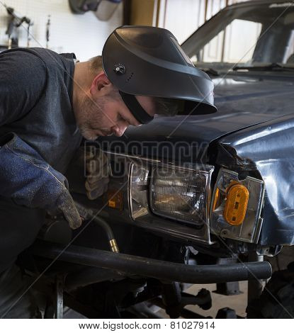 Man with welding tool in front of truck