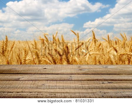 Old Wooden Table With Wheat Field Background. Shallow Depth Of Field