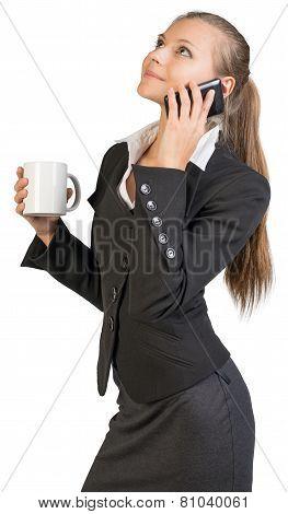Businesswoman holding mug, talking on the phone