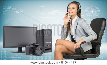 Businesswoman in headset, desktop computer and camera beside