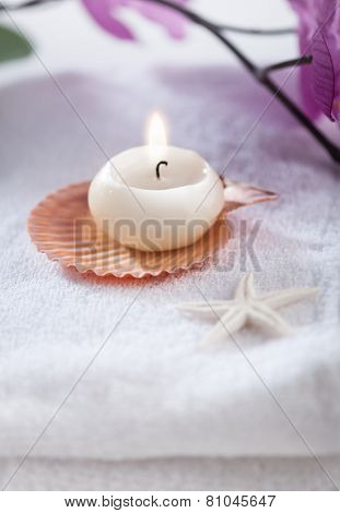 Burning candle with natural shells placed on white towel - spa object