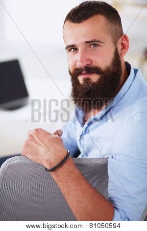 Young male office worker sitting on chair in office , isolated